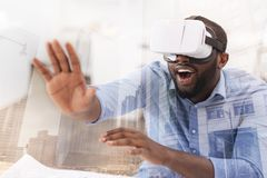Surprised man wearing virtual glasses. Unreal emotions. Close up of young African American wearing virtual glasses while putting his palm forward and expressing Stock Photos