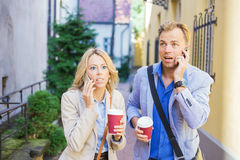 Surprised man and woman talking on the phone Royalty Free Stock Images