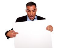 Surprised manager looking and pointing a card Stock Photography