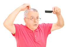 Surprised mature man holding a comb Royalty Free Stock Photos