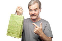 Surprised mature man holding shopping bag isolated on white. Background Royalty Free Stock Photography