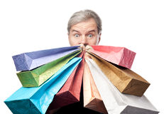 Surprised mature man holding shopping bags near face isolated Royalty Free Stock Photography