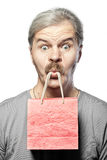 Surprised mature man with shopping bag in mouth isolated Royalty Free Stock Images