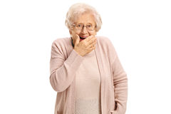 Surprised mature woman holding her hand against her mouth Royalty Free Stock Images