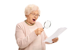 Surprised mature woman looking at a document through magnifying Royalty Free Stock Photography