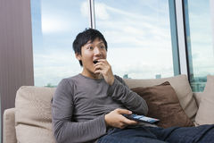 Surprised mid-adult man watching television on sofa at home Royalty Free Stock Photo