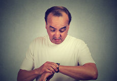 Surprised middle aged man looking at his wristwatch Royalty Free Stock Photos