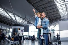 Surprised middle-aged man is standing with small girl at terminal. Feeling wonder. Low angle of curious pretty daughter is pointing out to something interesting Stock Image