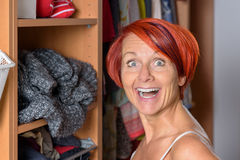 Surprised Middle Aged Woman in front of her wardrobe Stock Photography