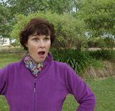 A Surprised Middle Aged Woman. A middle aged woman stares in surprise at something she has seen outdoors stock photo