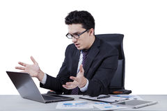 Surprised middle eastern worker looking at laptop royalty free stock photography