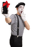 Surprised mime showing a phone wrapped with red ribbon Royalty Free Stock Photo