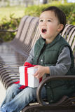Surprised Mixed Race Boy Opening A Christmas Gift Outdoors Stock Image