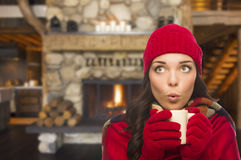 Surprised Mixed Race Girl Enjoying Warm Fireplace and Holding Mug Stock Images