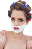 Surprised model in hair curlers posing with shaving foam Stock Photo