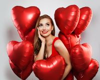 Surprised model woman with red balloons on white background. Cheerful girl with red lips makeup smiling and looking up. Surprise,