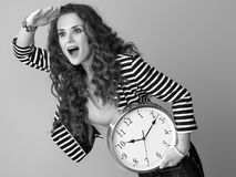 Surprised modern woman with clock looking into distance Royalty Free Stock Photo