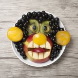 Surprised monkey made with fresh fruits on plate and board. Monkey made with currant, apple, kiwi and banana. Funy idea for making decorative figure from fruits royalty free stock photography