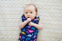 Surprised 1 month old baby girl lying on knitted blanket Stock Photos