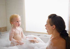 Surprised mother and baby in foam filled bathtub. Surprised young mother and baby in foam filled bathtub Royalty Free Stock Photography