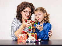 Surprised mother and daughter Christmas present and decorations Royalty Free Stock Image
