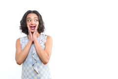 Surprised mulatto girl with hands near her chin. So surprised. Young mulatto girl showing astonishment on her face and touching her chin with hands on isolated Stock Photos