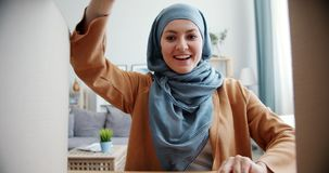 Surprised Muslim girl in hijab opening box looking inside expressing happiness. Surprised Muslim girl in hijab is opening box and looking inside expressing stock video