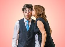 Surprised nerd is being kissed by pretty woman.  Stock Images