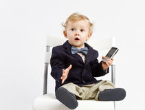 Surprised office baby. Little office baby dressed in business outfit with a bow and mobile phone, acting surprised royalty free stock images