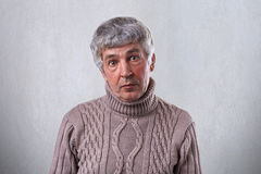 A surprised old man with dark eyes having wrinkles on his face and gray hair wearing brown sweater looking directly into camera wi Royalty Free Stock Photo