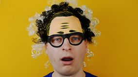 Surprised and open-eyed curly man, funny cheerfully human emotions, on yellow wall background, black and white hairs