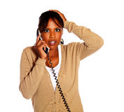 Surprised pensive female speaking on phone Stock Photo