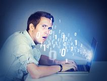Perplexed man with laptop learning computer science Stock Image