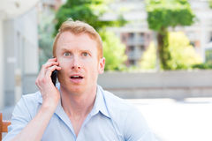 Surprised on phone. Closeup portrait,  young man, shocked surprised, wide open mouth, by what he hears on the cell phone, isolated outdoors building background Royalty Free Stock Photo