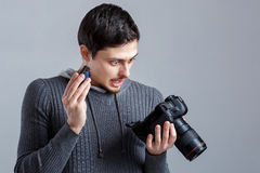 Surprised photographer is trying to insert the battery in DSLR d Stock Photo
