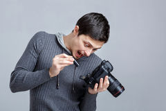 Surprised photographer is trying to insert the battery in DSLR d Royalty Free Stock Image