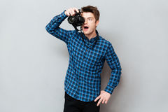 Surprised photographer working. Surprised young man photographer working with camera royalty free stock photos