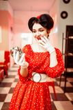 Surprised pin up girl looks at the alarm clock. Vintage cafe interior on background, popular american fashion 50s and 60s. Red dress with polka dots, bright Royalty Free Stock Photo
