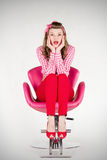 Surprised pin-up girl sitting on the chair. Surprise and pin-up girl sitting on the chair royalty free stock images