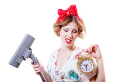 Surprised pinup girl beautiful blond young housewife holding vacuum cleaner & showing 9.30 on alarm clock. Picture of surprised blond young pretty woman Stock Images