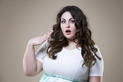Surprised plus size fashion model, fat emotional woman on beige background, overweight female body. Surprised plus size fashion model, fat emotional woman on Stock Image