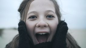 Surprised portrait of a happy girl close-up with a delighted facial expression. Mom covers her daughter`s eyes to surprise stock footage