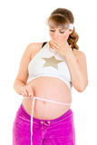 Surprised pregnant woman measuring her belly Stock Photos