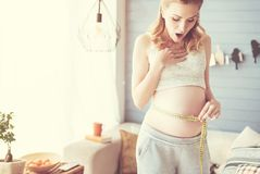 Surprised pregnant woman measuring her belly stock photography