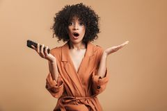 Surprised pretty african woman holding smartphone and looking at camera royalty free stock photo
