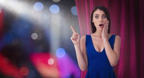 Pretty woman in front of red curtains indicates something about the theater show stock images