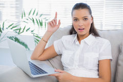Surprised pretty woman using laptop sitting on cosy sofa Stock Photography