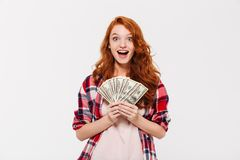 Surprised pretty young redhead lady holding money. Stock Image