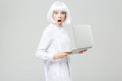 Surprised pretty young woman with opened mouth holding laptop Royalty Free Stock Photo