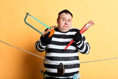 Surprised puzzled burglar choosing a tool to cut the chain. Isolated yellow bacakground. studio shot. man making decision before commiting crime. to steal or royalty free stock image